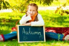 Écolière avec des pommes en automne Photographie stock