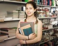 Écolière choisissant les cahiers colorés dans le magasin Image stock