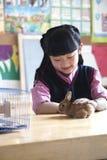 Écolière choyant le lapin d'animal familier dans la salle de classe Image stock