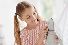 Écolière consciente donnant des écouteurs avec la musique jouant au jouet préféré Image libre de droits