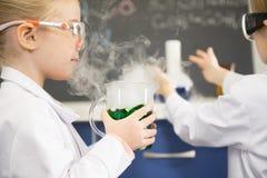 Écolière dans des protecteur de lunettes tenant le flacon avec l'échantillon chimique image stock