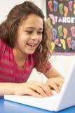 Écolière dans LUI classe utilisant l'ordinateur Photographie stock