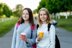 Écolière de deux belle jeunes filles En été en dehors de ville en air frais Il tient le thé et le café chauds dans des ses mains Images libres de droits