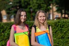 Écolière de deux filles Été en nature Sourire heureusement Préparez pour des leçons d'école Dans des mains d'un dossier avec des  Photographie stock