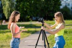 Écolière de deux filles Été en nature Vidéo record sur l'appareil-photo Conduit une émission visuelle sur l'Internet Le concept Photographie stock libre de droits