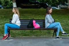 Écolière de deux filles En été ils se reposent sur un banc dans la ville Le concept de la querelle, conflit, problème, ressentime Photographie stock libre de droits