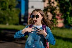 Écolière de fille Été en nature Dans la veste de denim avec le dos du sac à dos sunglasses Le concept de la surprise photos stock