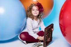 Écolière de fille avec l'abaque en bois et un bouchon des dollars Photos stock
