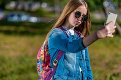 Écolière de fille en été en parc après école Dans des ses mains tient un smartphone Fait des gestes la communication sur un mobil Photographie stock libre de droits