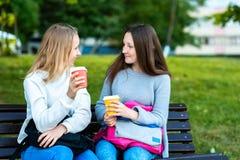 Écolière de filles sur un banc Les meilleurs amis en été se garent à l'air frais Il tient le café et le thé chauds femelle Photographie stock