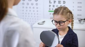 Écolière de froncement de sourcils refusant de porter des lunettes, opticien aidant à choisir l'eyewear banque de vidéos