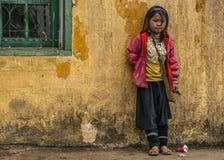 Écolière de Hmong se tenant contre le mur jaune Photographie stock libre de droits