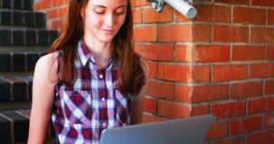 Écolière de sourire à l'aide de l'ordinateur portable sur l'escalier clips vidéos