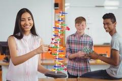Écolière de sourire étudiant le modèle de molécule dans le laboratoire Image libre de droits