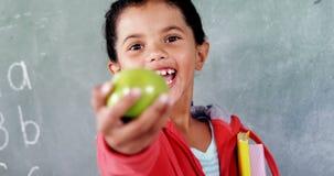 Écolière de sourire montrant la pomme dans la salle de classe banque de vidéos