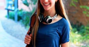 Écolière de sourire se tenant avec le cartable dans le campus clips vidéos