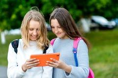 Écolière deux d'amie Été en nature Dans des ses mains tient un comprimé Derrière le sac à dos Le concept de l'observation Photo stock