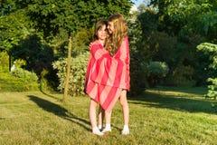 Écolière deux de petite amie 7-8 ans embrassant jouer sur le pré en parc Photographie stock