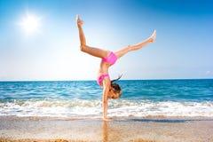 Écolière effectuant la gymnastique sur le bord de la mer ou la plage Photos libres de droits
