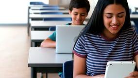 Écolière et écolier à l'aide de l'ordinateur portable et du comprimé numérique tout en étudiant dans la salle de classe banque de vidéos