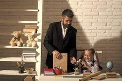 Écolière et son papa avec le microscope heureux d'utilisation de visages photographie stock libre de droits