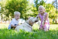 Écolière et un petit garçon jouant avec un chien images libres de droits