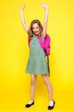 Écolière Excited posant avec des bras augmentés Image stock