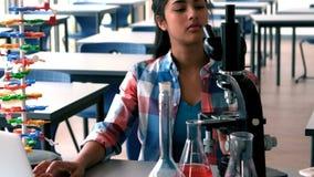 Écolière expérimentant sur le microscope dans le laboratoire banque de vidéos