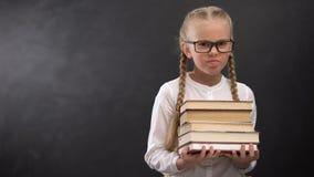 Écolière futée dans des lunettes tenant à peine le tas des livres contre le tableau noir banque de vidéos