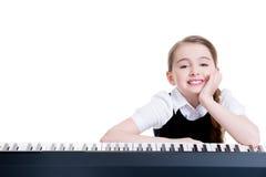 Écolière heureuse avec le piano électrique. Image stock