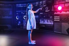 Écolière heureuse ayant un jour productif et indiquant le dispositif futuriste image stock