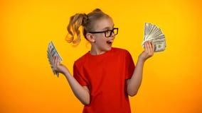 Écolière heureuse regardant des groupes d'argent liquide du dollar, élève futé recevant la concession images libres de droits