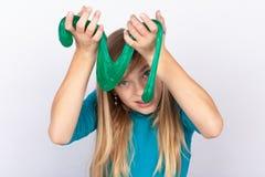 Écolière mignonne avec le jouet vert de boue images stock