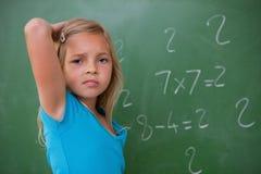 Écolière pensant tout en rayant le dos de sa tête photo stock