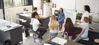 Écolière présent devant la classe de la science, courbe image stock