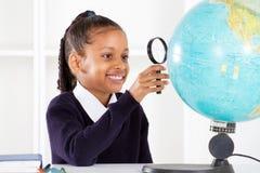 Écolière regardant le globe Photographie stock