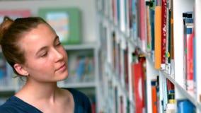 Écolière sélectionnant le livre des étagères à livres dans la bibliothèque clips vidéos
