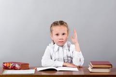 Écolière s'asseyant au bureau soulevant sa main connaissant l'answ image libre de droits