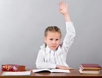 Écolière s'asseyant au bureau soulevant sa main connaissant l'answ photo stock