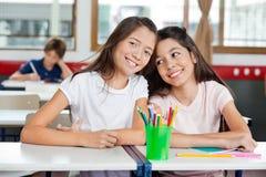 Écolière s'asseyant avec l'ami féminin au bureau dedans Images libres de droits
