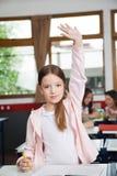 Écolière soulevant la main tout en se tenant dedans Photographie stock libre de droits