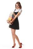 Écolière sur un fond blanc avec une pile des livres dans des mains Photos stock