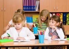 Écolière trichant à l'examen, regardant l'écriture d'un ami Images stock