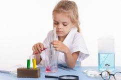 Écolière versant le liquide rouge un flacon dans la classe de chimie Images libres de droits