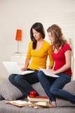 Écolières apprenant sur le divan à la maison Photos libres de droits