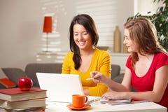 Écolières heureuses apprenant avec l'ordinateur Images stock