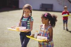 Écolières heureuses tenant le repas dans le plateau images stock
