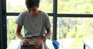 Écolier à l'aide de l'ordinateur portable dans la salle de classe banque de vidéos