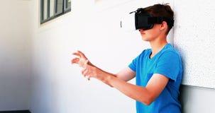 Écolier à l'aide du casque de réalité virtuelle dans le couloir clips vidéos