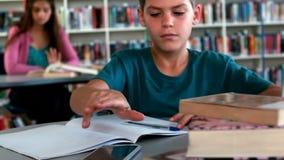Écolier à l'aide du téléphone portable tout en étudiant dans la bibliothèque clips vidéos